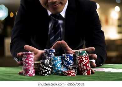 Close up at Gambler man used hands pushing large stack of colored poker chips across gaming table for betting on casino club background