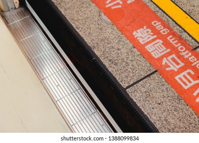 """Close up of the gap between a metro train and platform. TRANSLATION - sign said """" Mind the platform gap"""" in Chinese and English"""
