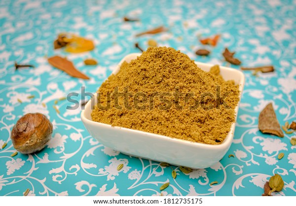 Close up of Garam Masala Powder in a bowl on a floral background table along with spices as props