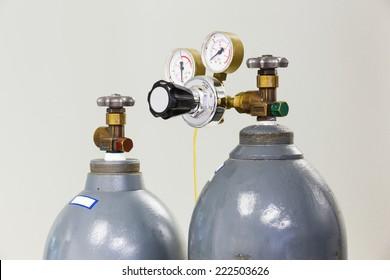 Close up gauges and valve on old nitrogen gas cylinder in laboratory