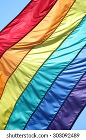 Close Up of a gay pride flag against a blue sky