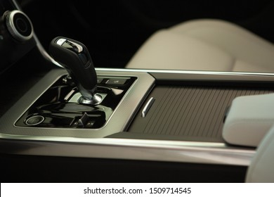 Close up of a gear shift box in a new automobile. Manual gearbox transmission handle closeup shot. Accelerator handle and buttons in a new car. Automatic transmission handle