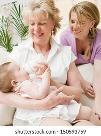 Close up of a generational family together in their living room at home, relaxing with the grandmother enjoying the feeding of her new baby girl grand daughter feeling proud.