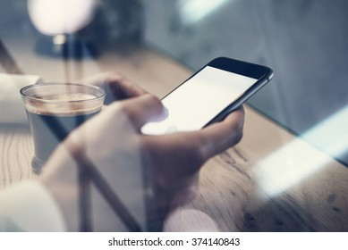 Close up of generic design smart phone holding in female hands for texting message. Cup coffee on the table