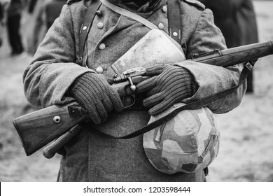Close Up Of German Military Ammunition Of A German Wehrmacht Soldier At World War II. Warm Autumn Clothes, Soldier's Overcoat, Gloves, Helmet, Sapper Shovel, Rifle. Photo In Black And White Colors.