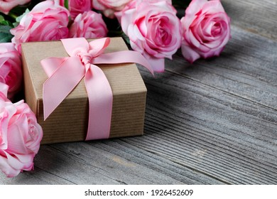 Close up of a gift box with pink roses in background on weathered wooden planks for Mothers day love holiday concept