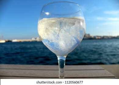 Close up of gin tonic glass (full) in Ibiza with old town view, ice cubes and blurry background