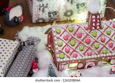 Close up of a gingerbread house and some gifts and christmas decorations around