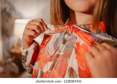 Close up of girl adjusting her bow tie in orange blouse. Elegant girl model poses in blouse and bow tie.