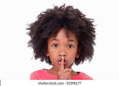 Close up of a girl asking silence against a white background