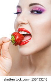 Close up of girl with bright pink make-up and red lips eating strawberry, isolated on white. Concept of beauty and healthy food