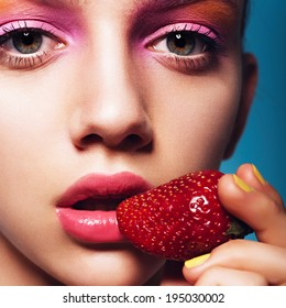 Close up of girl with brilliant pink make-up eating strawberry. Concept of beauty and healthy food, blue background.