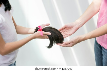 Close up of girl hand donating her healthy hair to cancer patients. Asian kid holding,  giving her ponytail after haircut, generously donating her long hair for making wigs to cancer patient lost hair