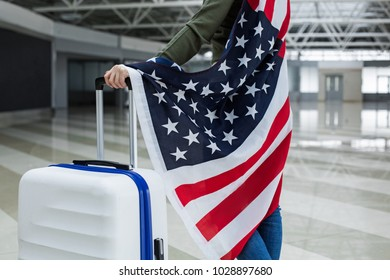 Close up of girl hand holding bag in the terminal. American banner is on her back