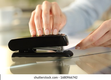 Close up of girl hands using stapler on documents over a desk at home