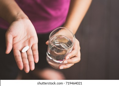 Close Up Of Girl holding Pill and glass of water.With Paracetamol.Nutritional Supplements.Sport,Diet Concept.Capsules Vitamin And Dietary Supplements.