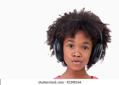 Close up of a girl listening to music against a white background