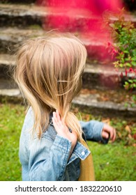 A close up of a girl looking away while adjusting her long blonde hair with her right hand. Hair blown away on a windy day. A child playing in an english garden. Distracted girl. - Shutterstock ID 1832220610