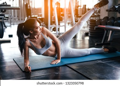 Close up girl meditating indoors.Meditation and lotus concept.Woman exercising yoga at sunset with warmth background in gym.