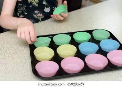 close up of a girl putting colour cup cake cases into a baking tray