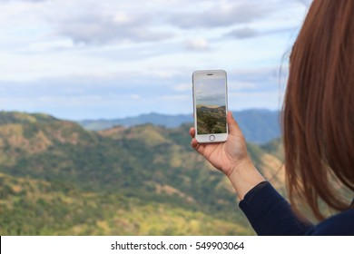 Close up of a girl using mobile smart phone take photography of view