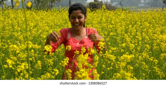 Close up of a girl wearing a red salwar  laughing heartly in a sunny day in a rapeseed, mustard flower field with lots of yellow flowers