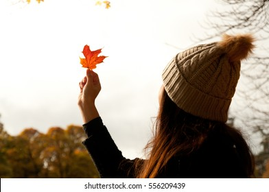 Close up of a girl wearing a woolly hat looking at a red leaf held high in front of her and into the sun, near River Tummel in Pitlochry, Scotland, under a yellow leafed tree.
