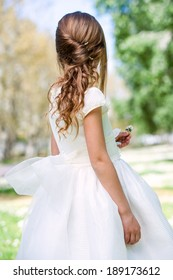 Close up of girl in white dress showing hairstyle outdoors.