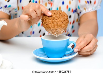 Close up of girl's hands dipping oat cookie in cup with milk.
