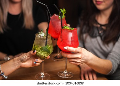 Close up of girls drinking cocktails in nightclub. Girls having good time,cheering and drinking cold cocktails, enjoying friendship together in bar, close up view on hands.