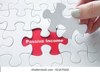 Close up of girl's hand placing the last jigsaw puzzle piece with word Passive Income