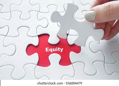 Close up of girl's hand placing the last jigsaw puzzle piece with word Equity