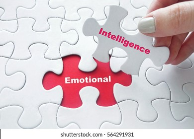 Close up of girl's hand placing the last jigsaw puzzle piece with word Emotional Intelligence