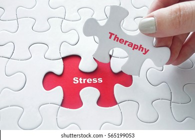 Close up of girl's hand placing the last jigsaw puzzle piece with word Stress and Therapy as Stress Relief Technique