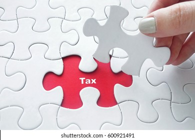Close up of girl's hand placing the last jigsaw puzzle piece with word Tax