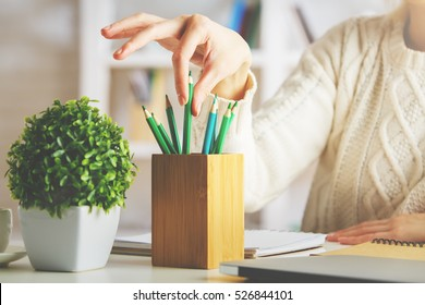 Close up of girl's hand taking green pencil out of holder on blurry shelf background