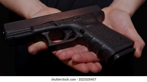 A close up of a girl's hands holding a black pistol on a black background