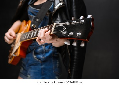 Close up of girl's hands on guitar over black background in jeans