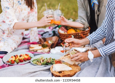 Close up girls spending time on beautiful picnic with variety of tasty food and drinks on picnic blanket in park