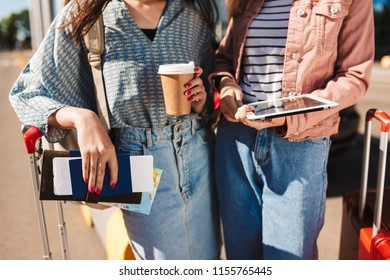 Close up girls with suitcases holding coffee to go,passports with tickets and the tablet in hands in airport outdoor