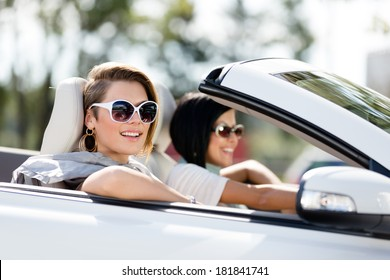 Close up of girls wearing sunglasses in the auto. Little holiday trip of friends