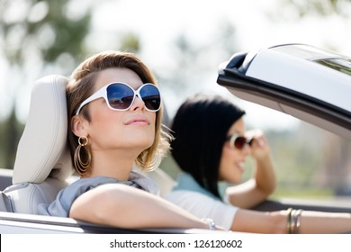 Close up of girls wearing sunglasses in the white car. Little holiday trip of friends