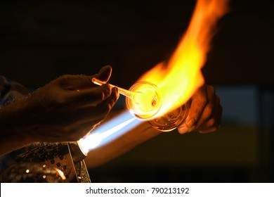 close up of glass blower using a glassblowing torch
