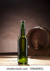 Close up of a glass bottle of beer on wooden table and brown background