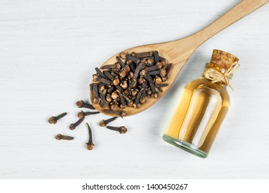 Close up glass bottle of clove oil and cloves in wooden spoon on white rustic table. Essential oil of clove rustic style background spice concept  - Shutterstock ID 1400450267