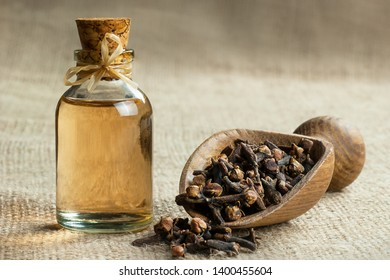 Close up glass bottle of clove oil and cloves in wooden shovel on burlap sack. Essential oil of clove rustic style background spice concept