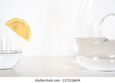 close up of glass and bottle of water with lemon slice on a whit