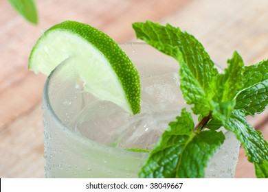 Close up of glass of cold drink with slice of lime