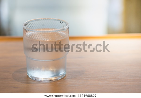 Close up of glass of cold water on wooden table.