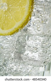 Close up of glass containing sparkling clear liquid and ice cubes and lemon slice